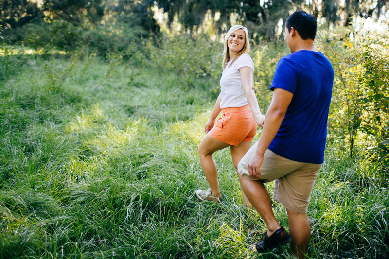 LAKELAND ENGAGEMENT SESSION: girl leading guy into grassy field